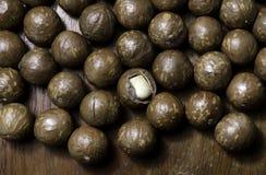 Macadamiamutter på den wood tabellen Arkivfoto