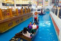 MACAO KINA MAY 11, 2017: Ett oidentifierat kinesiskt folk som har en tur i en venetian gondol inom av ett härligt Arkivfoton