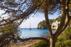 Macarella wyrzucać na brzeg widzii wśród drzew na pogodnym ranku, Minorca Zdjęcie Stock