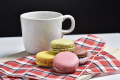 Macaron με το φλυτζάνι καφέ στο μαύρο υπόβαθρο Στοκ Φωτογραφία