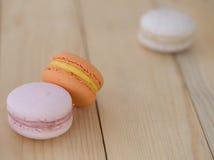特写镜头橙色蛋白杏仁饼干,在木背景的Macaron 免版税库存照片