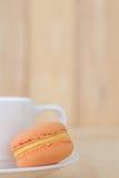 橙色蛋白杏仁饼干,与杯子的Macaron在木背景 库存图片