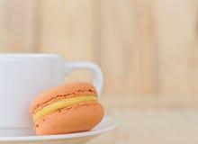 Macaron alaranjado, bolinho de amêndoa com o copo no fundo de madeira Imagens de Stock Royalty Free