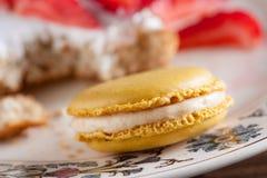 Macaron amarelo delicioso em um prato romântico bonito Foto de Stock Royalty Free