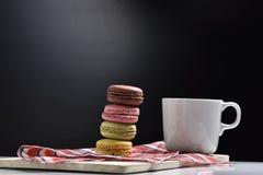 Macaron avec la tasse de café sur le fond noir Photographie stock libre de droits