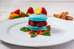 Macaron bleu avec des framboises Photographie stock