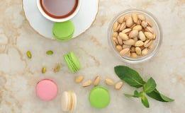 Macaron coloré avec une tasse de thé Images stock