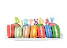 Macaron cookies birthday party plate isolated. Many colorful macaron cookies on a white rectangular plate, birthday candles spelling the word BIRTHDAY isolated stock photography