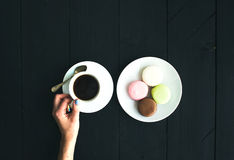 Macaron cookies, cup of espresso and ladie's hands over black wooden backdrop Stock Images