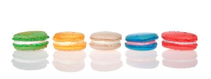 Macaron cookies lined up in a row isolated in reflective surface. Row of macaron cookies laying sideways side by side multiple colors and flavors on a reflective royalty free stock photography