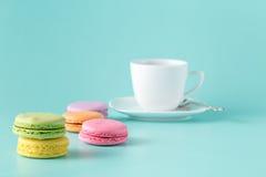 Macaron de couleur en pastel avec du café sur le fond bleu vert Images libres de droits