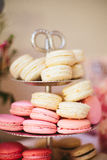 Macaron Display at Wedding Reception. A stacked display of white, pink and chocolate macarons on a silver tray at a wedding dessert buffet table with a love Royalty Free Stock Photography
