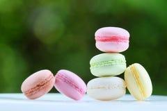 Macaron en color en colores pastel con el fondo verde de la falta de definición Fotos de archivo