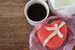 Macaron en forme de coeur, café, fond en bois Photos stock
