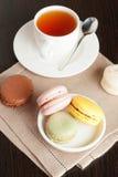 Macaron français coloré avec la tasse de thé sur le fond noir Photos stock