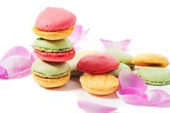 Macaron kakor och rosa färgroskronblad Royaltyfri Bild