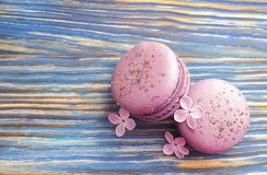Macaron or macaroon french coockie on dark blue  background with purple flowers, pastel colors. Flat lay. Food concept. Sweet and colourful french macaroons or Royalty Free Stock Photography
