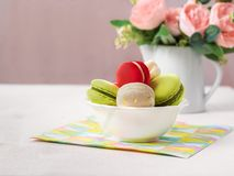 Macaron or macaroon french coockie on light background with spring flowers, pastel colors with copy space stock image