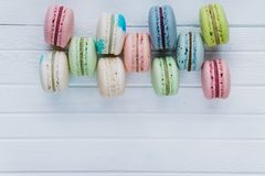 Macaron or macaroons or almond cookies lie on a wooden white background. Top view close-up, copy space. Macaron or macaroons or almond cookies lie on a wooden Stock Images