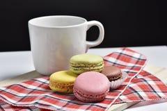 Macaron med kaffekoppen på svart bakgrund Arkivbild