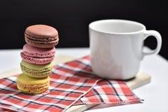 Macaron med kaffekoppen på svart bakgrund Royaltyfria Foton