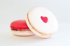 Macaron mit rotem Herzen auf einem weißen Hintergrund Stockbild