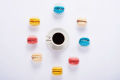 macaron multicolore autour de et café sur le fond blanc de Image stock