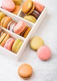 Macaron o macarrones de la torta del postre en la caja de madera blanca en el fondo de piedra de la tabla de cocina Visión superi fotografía de archivo libre de regalías