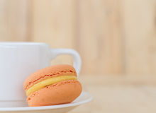 Macaron orange, macaron avec la tasse sur le fond en bois Images libres de droits