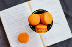 Macaron orange sur le journal intime ouvert Image stock