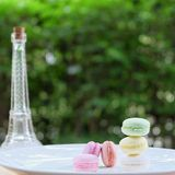 Macaron in pastel color with mini glass Eiffel and green blur background. Lovely pastel colors Macarons (focus on front pink one) with mini glass Eiffel and Royalty Free Stock Image