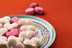 Macaron rose et crème sur le fond orange Photo libre de droits