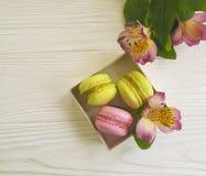 Macaron in una scatola su un fondo di legno bianco, flowe di alstroemeria Fotografia Stock Libera da Diritti