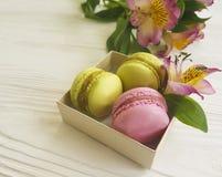 Macaron in una scatola sul fiore di legno bianco di alstroemeria del fondo della gastronomie Fotografia Stock Libera da Diritti