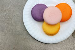 Macaron in white plates on the background of the cement. Stock Image