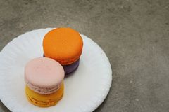 Macaron in white plates on the background of the cement. Stock Images