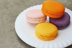 Macaron in white plates on the background of the cement. Royalty Free Stock Images