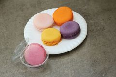 Macaron in white plates on the background of the cement. Stock Photography
