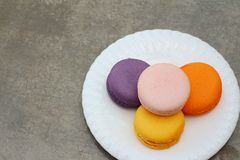 Macaron in white plates on the background of the cement. Royalty Free Stock Photos