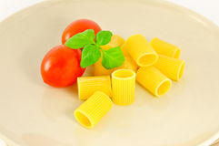 Macaroni. Pasta with tomato and basil. Raw ingredients Royalty Free Stock Photo