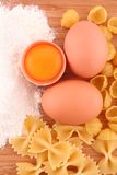 Macaroni. Eggs and flour on kitchen board stock images