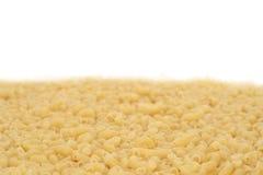 Macaroni background. Uncooked short ribbed pasta tubes - background Stock Images
