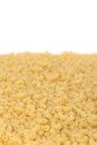 Macaroni background. Uncooked short ribbed pasta tubes - background Royalty Free Stock Photos