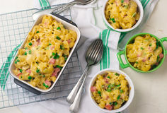 Macaroni baked pudding with ham and peas. Stock Photos