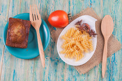 Macaroni and bread with fork and spoon royalty free stock image