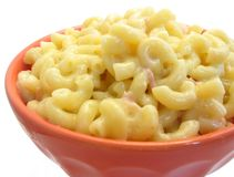 Macaroni and cheese. Bowl of macaroni and cheese on white, with ham and pepper Stock Image