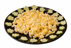 Macaroni cheese and cucumber are on a black plate. Some macaroni cheese and cucumber are on a black plate royalty free stock photo