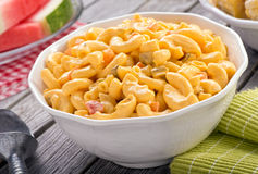 Macaroni and Cheese Salad. A bowl of delicious creamy macaroni and cheese salad on a rustic picnic table with watermelon and corn Stock Photo