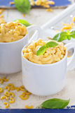 Macaroni and cheese served in mugs Stock Photos