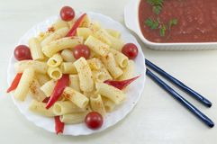 Macaroni with cherry tomatoes and red pepper served with a tomat Stock Photos